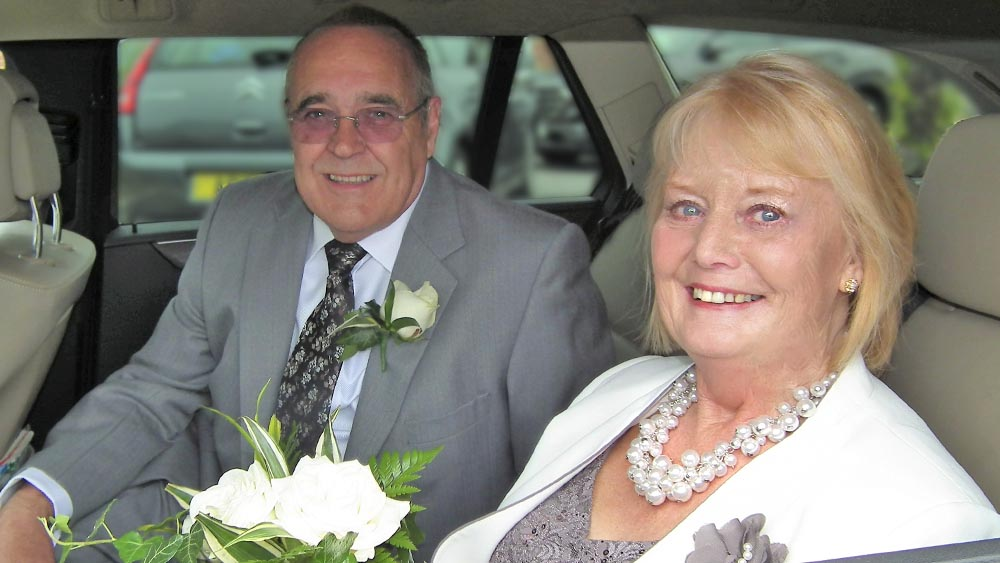 Paulene transanal irrigation user wedding day sat in car with flower bouquet
